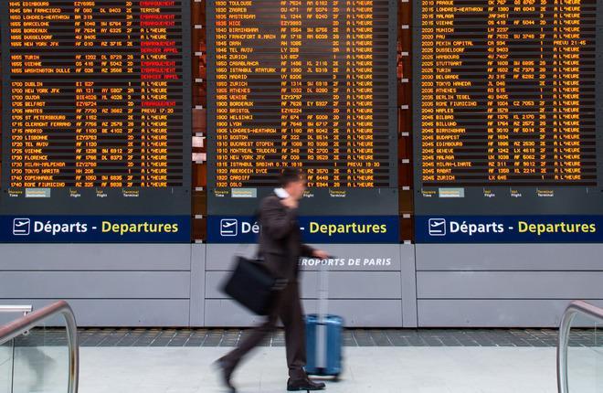 Авиапассажир в аэропорту у авиарасписания
