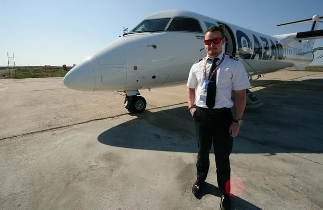 Пилот перед самолетом Bombardier Q400 New Generation авиакомпании Qazaq Air